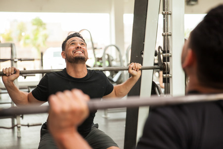 man gym: Young man doing a big effort to lift weight while working out on a squat machine at a gym