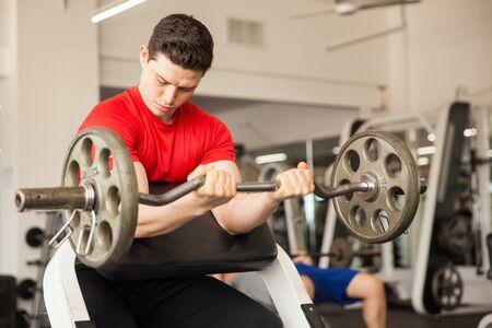 predicador: joven atractiva que hace flexiones de b�ceps en un banco predicador en el gimnasio Foto de archivo