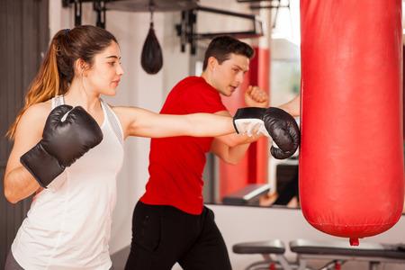 Goed uitziende jonge vrouw met bokshandschoenen oefenen op een bokszak naast haar instructeur