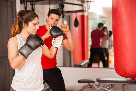Portrait of a gorgeous Hispanic brunette practicing boxing with her personal trainer at the gym