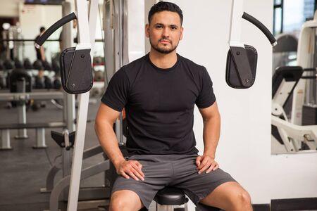 Portret van een jonge atletische man nemen een pauze van zijn training in de sportschool