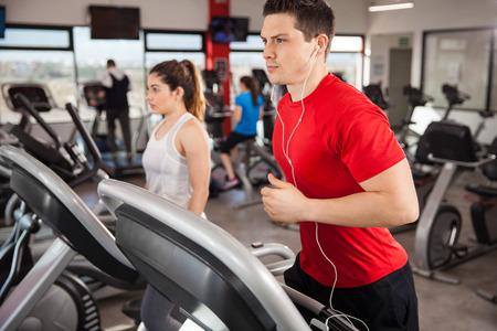 la escucha activa: Hombre joven atlético centrado en su carrera y escuchar música desde su teléfono inteligente Foto de archivo