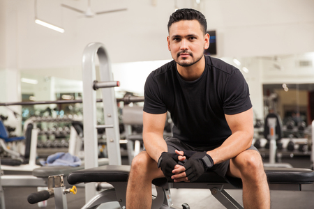 Portrait of an attractive young personal trainer sitting on a bench at the gym