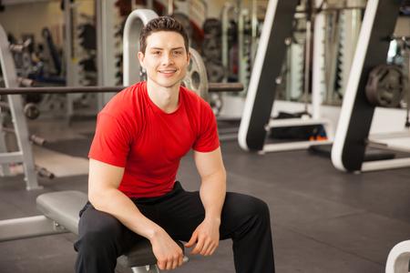 men exercising: Retrato de un hombre hispánico joven sentado en un banco en el gimnasio y sonriente Foto de archivo