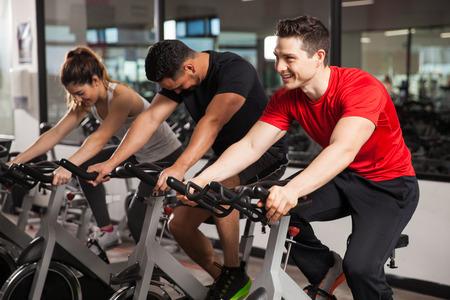 Groep van drie mensen genieten van hun draaiende sessie in de sportschool en glimlachen