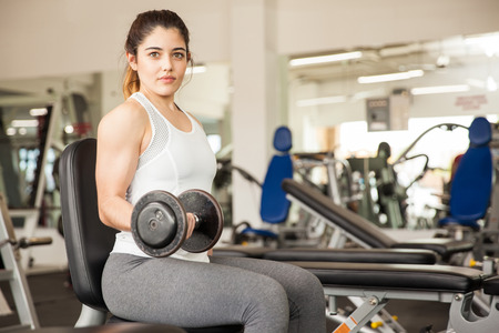 bicep: Portrait of a gorgeous young Hispanic woman lifting some weights and working on her biceps at the gym Stock Photo