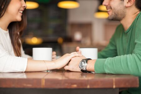 Closeup of an attractive young couple holding hands while drinking coffee during a date in a restaurant