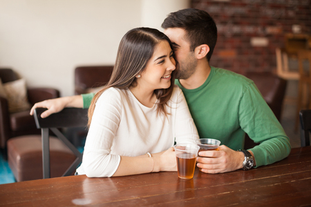 Young man flirting and whispering in a womans ear while drinking beer and having fun at a bar