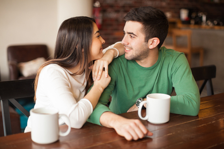 Young happy couple relaxing together and looking at each other while having some coffee in a restaurant