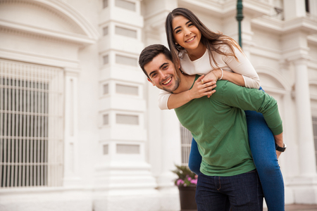 happy couple: Portrait of a good looking young and happy couple having fun with a piggyback ride in the city Stock Photo