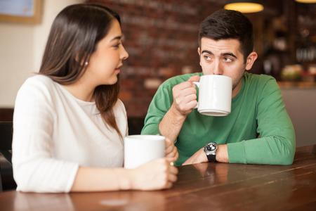 잘 생긴 젊은 부부 얘기하고 레스토랑에서 커피를 마시는