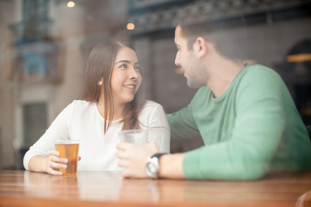 Pretty young woman drinking beer at a bar and talking to a guy Imagens