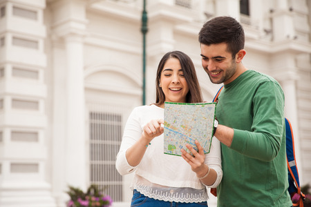 Good looking young Hispanic couple reading a map during a short trip they did together