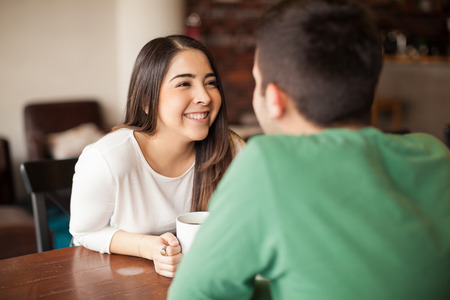 hispanic woman: Beautiful young woman smiling at her boyfriend while they both have some coffee at a restaurant
