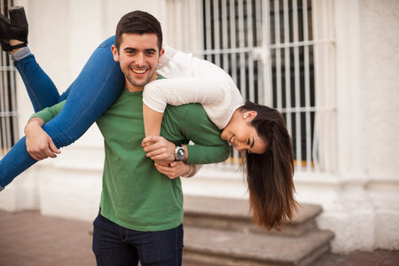 Good looking man with a beard carrying his girlfriend and having fun with her Imagens