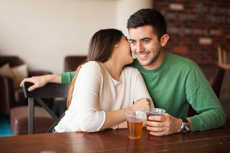 Pretty brunette whispering something on a mans ear while flirting and drinking beer in a bar