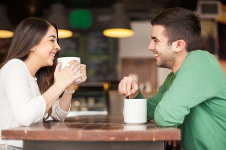 tomando café: Vista de perfil de un buen café mirando pareja de jóvenes bebiendo y divirtiéndose en un restaurante