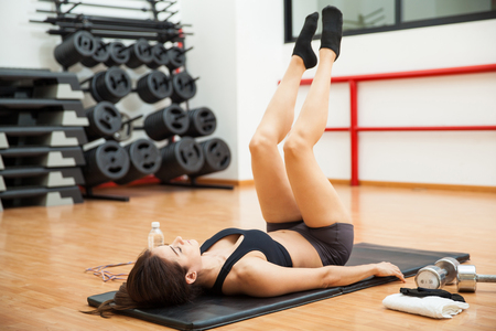 raises: Beautiful young woman doing leg raises and working on her abs at the gym