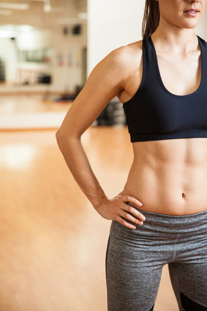 athletic body: Closeup of half of the body of a young and athletic woman showing her toned abs in a gym
