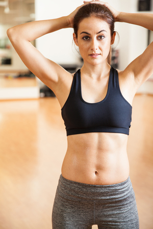 athletic body: Portrait of a strong Hispanic young woman in sporty outfit showing her athletic body with abs at the gym