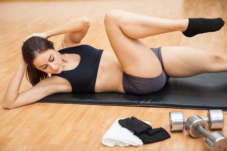 crossover: Athletic young woman doing crossover crunches as part of her fitness routine at the gym