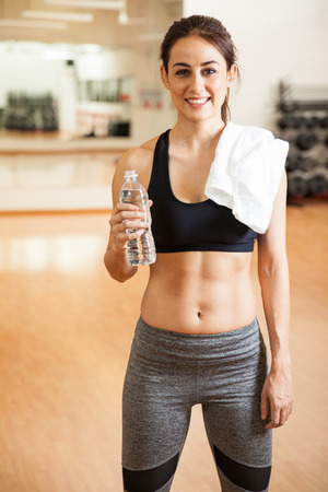 brunette girl: Portrait of a cute young brunette with toned abs holding a bottle of water and taking a break from her workout