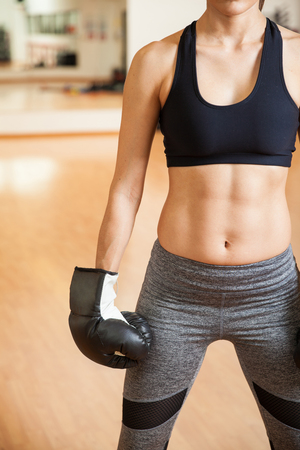 women sport: Closeup of a young woman with toned abs wearing boxing gloves in a gym. With some copy space on the side