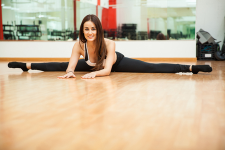 Portrait of a gorgeous young Hispanic woman doing a leg split at the gym and smiling. Tons of copy space Imagens - 54131894