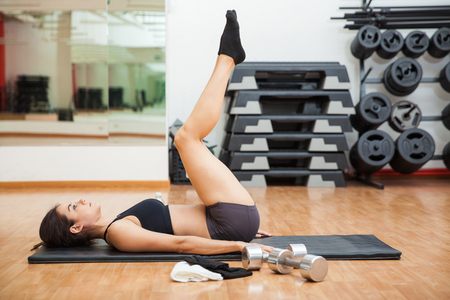 Profile view of a young athletic woman doing tabletop crunches at the gym