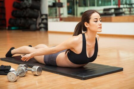 mujeres de espalda: Retrato de una mujer joven y centrarse en su entrenamiento y haciendo algo de revertir abdominales posterior enrollamiento en un gimnasio