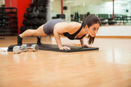 Athletic young brunette doing push ups at they gym. Lots of copy space