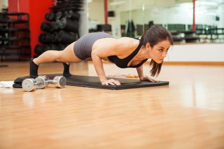 Atletische jonge brunette doet push ups op deze sportschool. Veel van de kopie ruimte