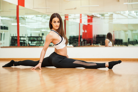split up: Beautiful young flexible woman doing a leg split at the gym and making eye contact