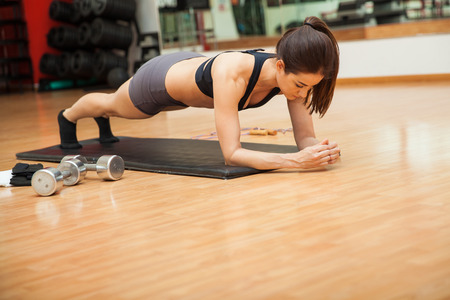 Athletic young woman holding a plank pose and working on her abs at the gym