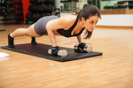 hispanic woman: Portrait of a beautiful athletic woman doing push ups and looking very focused on her workout