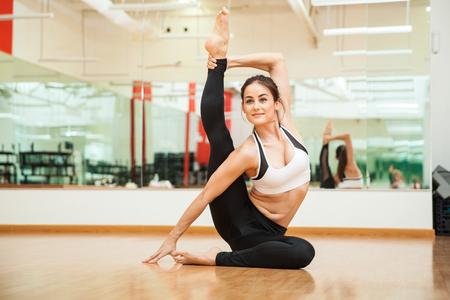 Portret van een leuke jonge vrouw die zich uitstrekt en het beoefenen van een aantal gymnastische bewegingen op de sportschool