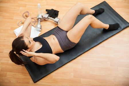 crunches: Young athletic brunette doing crunches at the gym and strengthening her abs, as seen from above