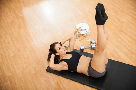 crunches: Top view of a young woman keeping her legs raised and doing crunches at the gym