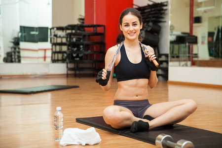jump rope: Pretty athletic young brunette holding a jump rope at the gym and smiling Stock Photo