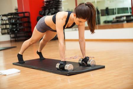 Leuke jonge brunette doet push ups in de sportschool terwijl een paar dumbbells