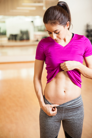 strong woman: Portrait of a beautiful young athletic brunette lifting up her shirt and showing off her abs at the gym