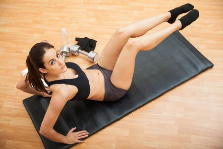 crunches: Top view of a pretty Latin woman doing seated crunches and working on her abs at the gym