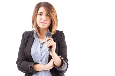 business conference: Beautiful, confident and successful young woman in a suit giving a presentation with a microphone Stock Photo