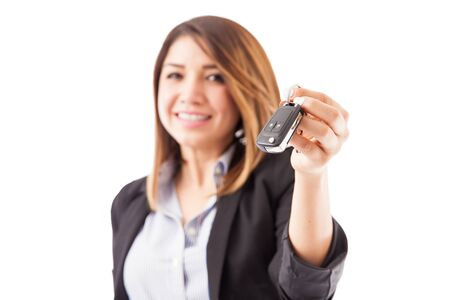 some: Closeup of a young female sales executive handing over some car keys to a customer. Focus on keys Stock Photo
