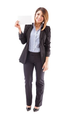 salesperson: Pretty young salesperson holding up a small sign in her hand and smiling on a white background Stock Photo
