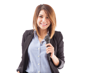 expositor: Portrait of a gorgeous young and successful woman holding a microphone during a seminar and smiling.