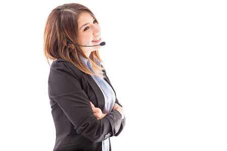 contact center: Profile view of a beautiful female telemarketer talking to a customer and smiling on a white background Stock Photo