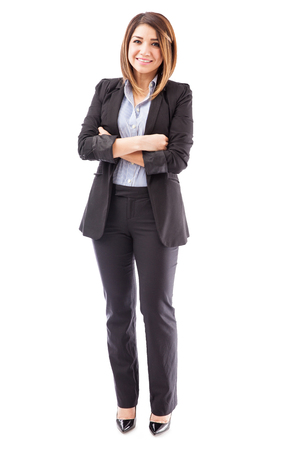 Beautiful young Hispanic salesperson wearing a suit and standing against a white background
