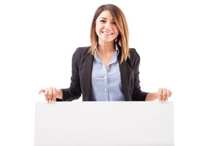 Beautiful young salesperson holding a big sign on a white background and smiling 写真素材