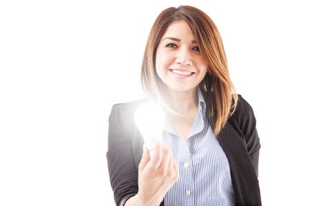 pensamiento creativo: joven y bella empresaria hispana sosteniendo una bombilla LED de encendido, lo que representa la creatividad